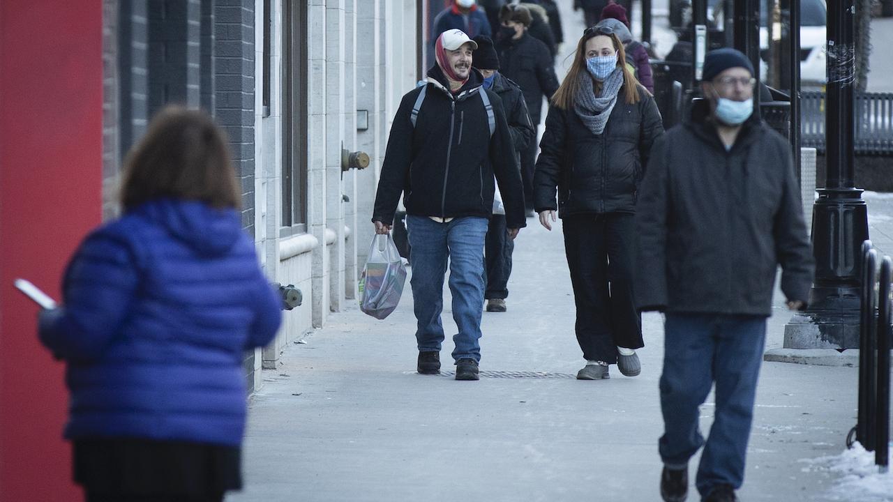 masked people walk down a street