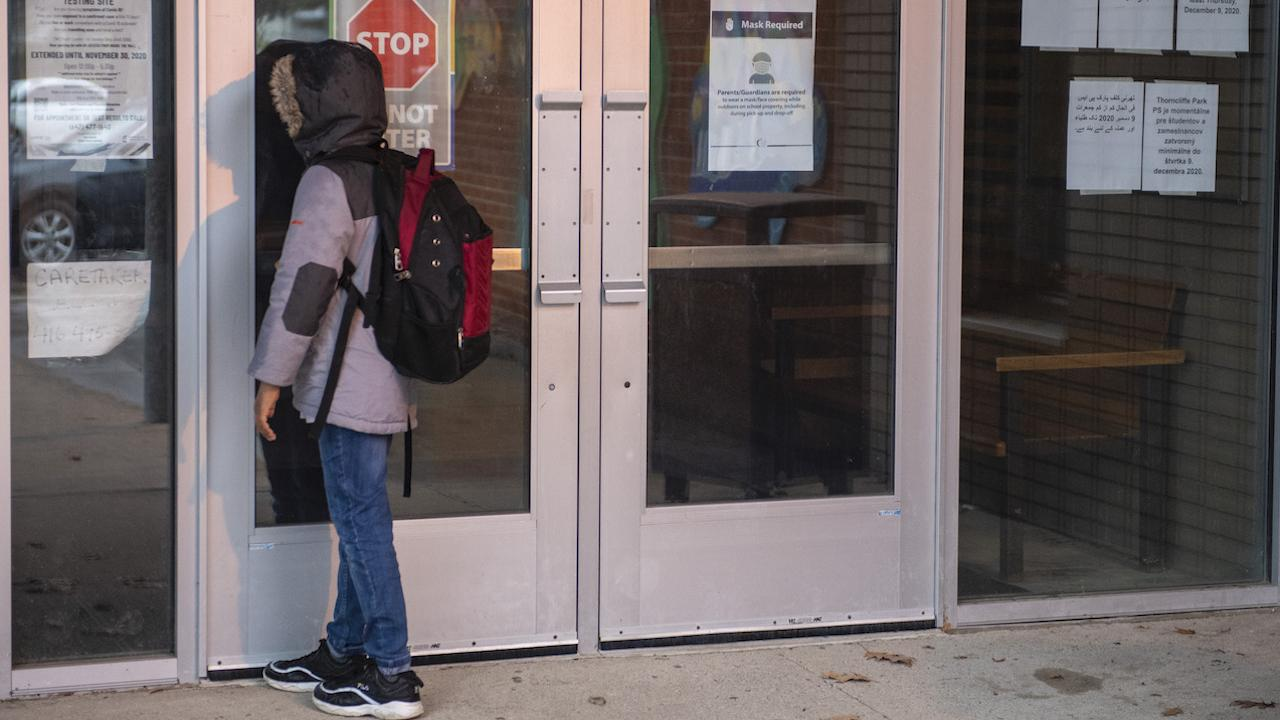 a youth in a backpack looks through the door of a closed school