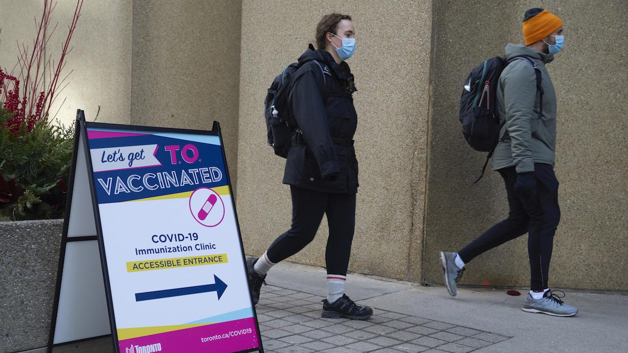 two masked people walk past a sign with information about vaccination