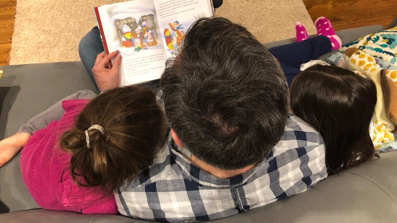 A man sits between his two daughters. They are reading a Winnie the Pooh book. Their faces are turned away from the camera.