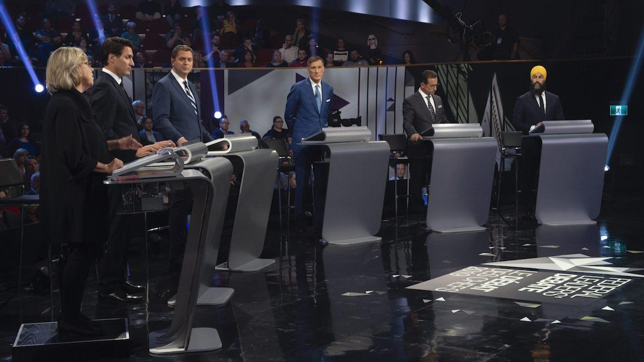 five men and one woman stand at podiums on a stage