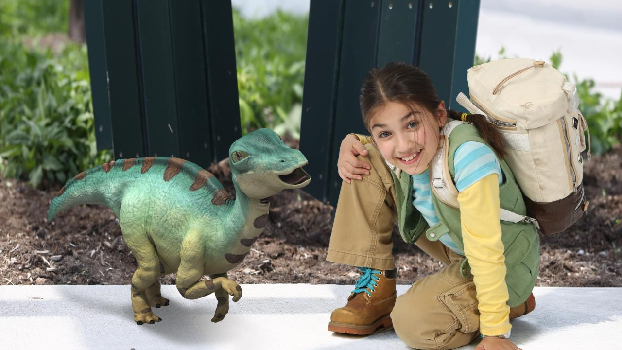 Nine-year-old girl crouches down next to an animation of a baby dinosaur