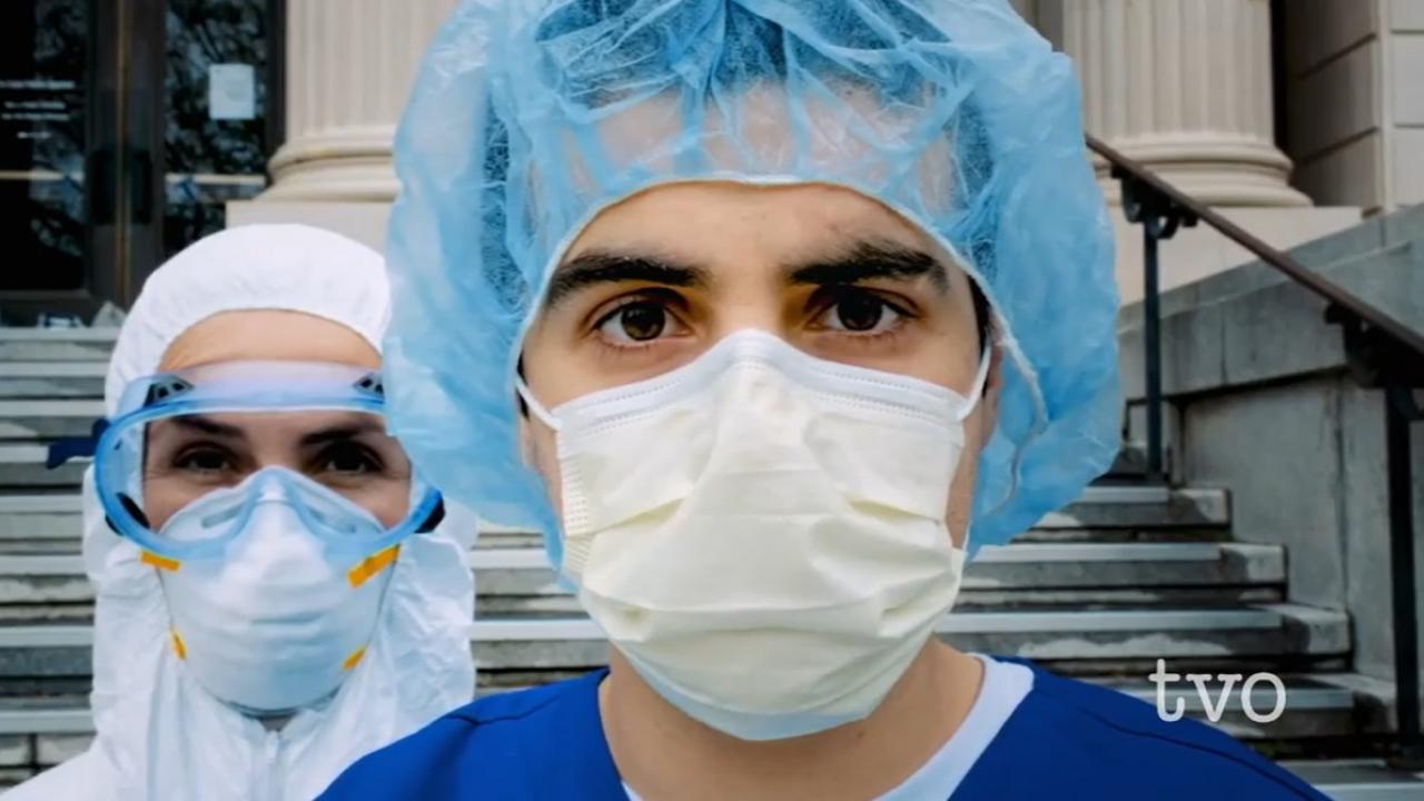 Two people in masks and hospital gear