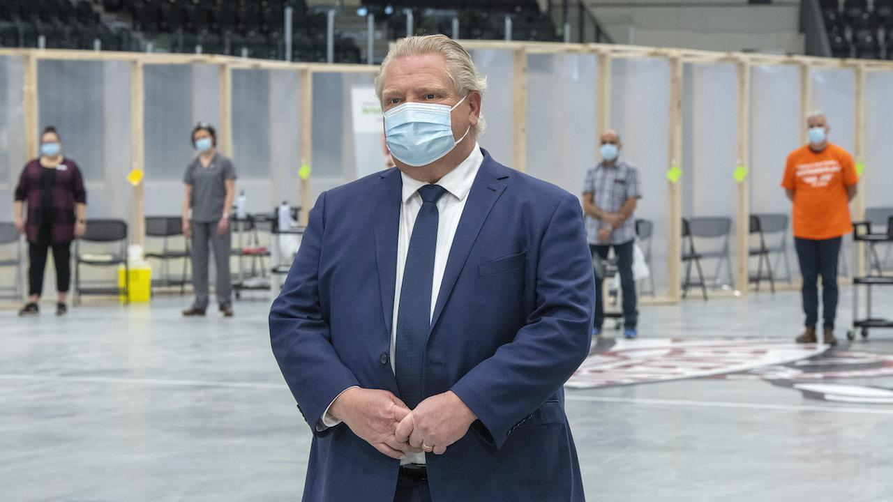 masked man in blue suit and tie stands in front of a row of people