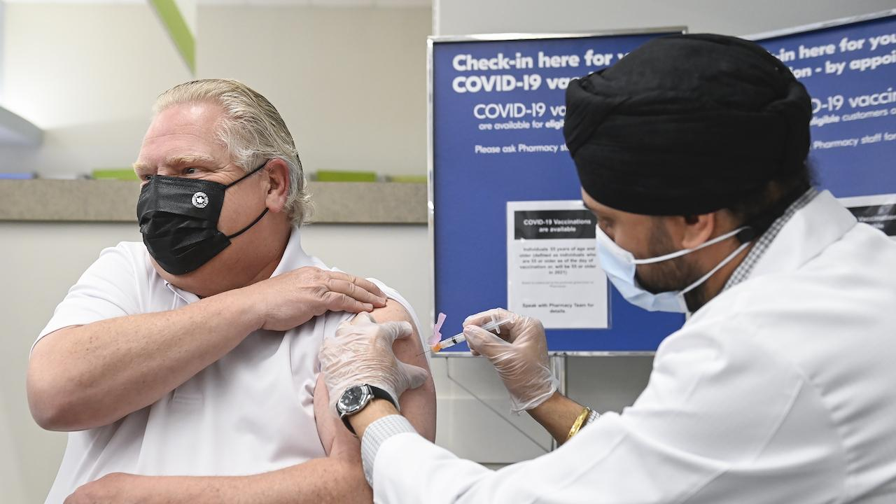 masked man rolls up sleeve to receive a needle from a masked man in a white jacket