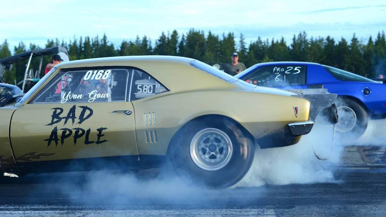 cars revving up at a drag race