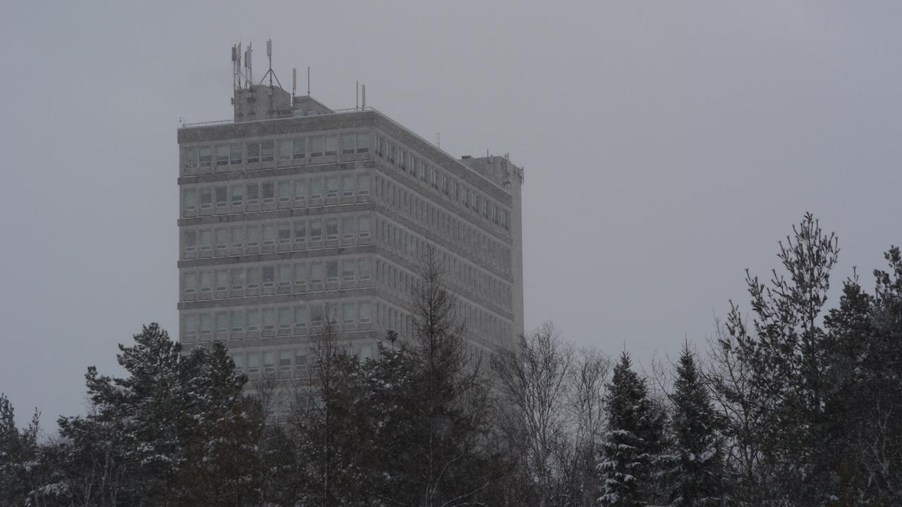 a tall concrete building behind snowy trees