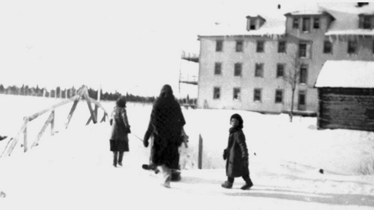an adult and three children walk down a snowy path by a building