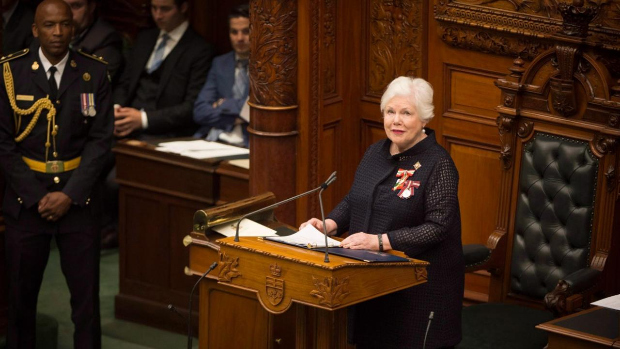 Woman stands at podium in front of Speaker's chair in the Ontario legislature.