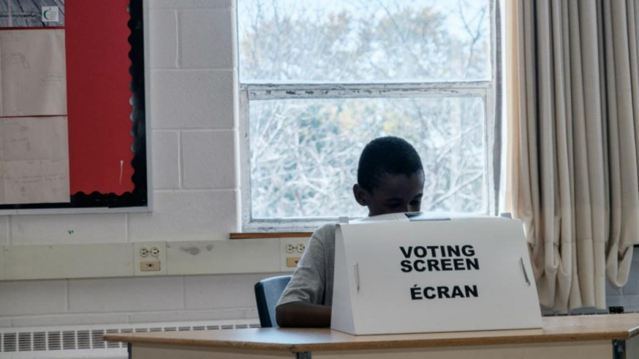 a student at a mock voting booth