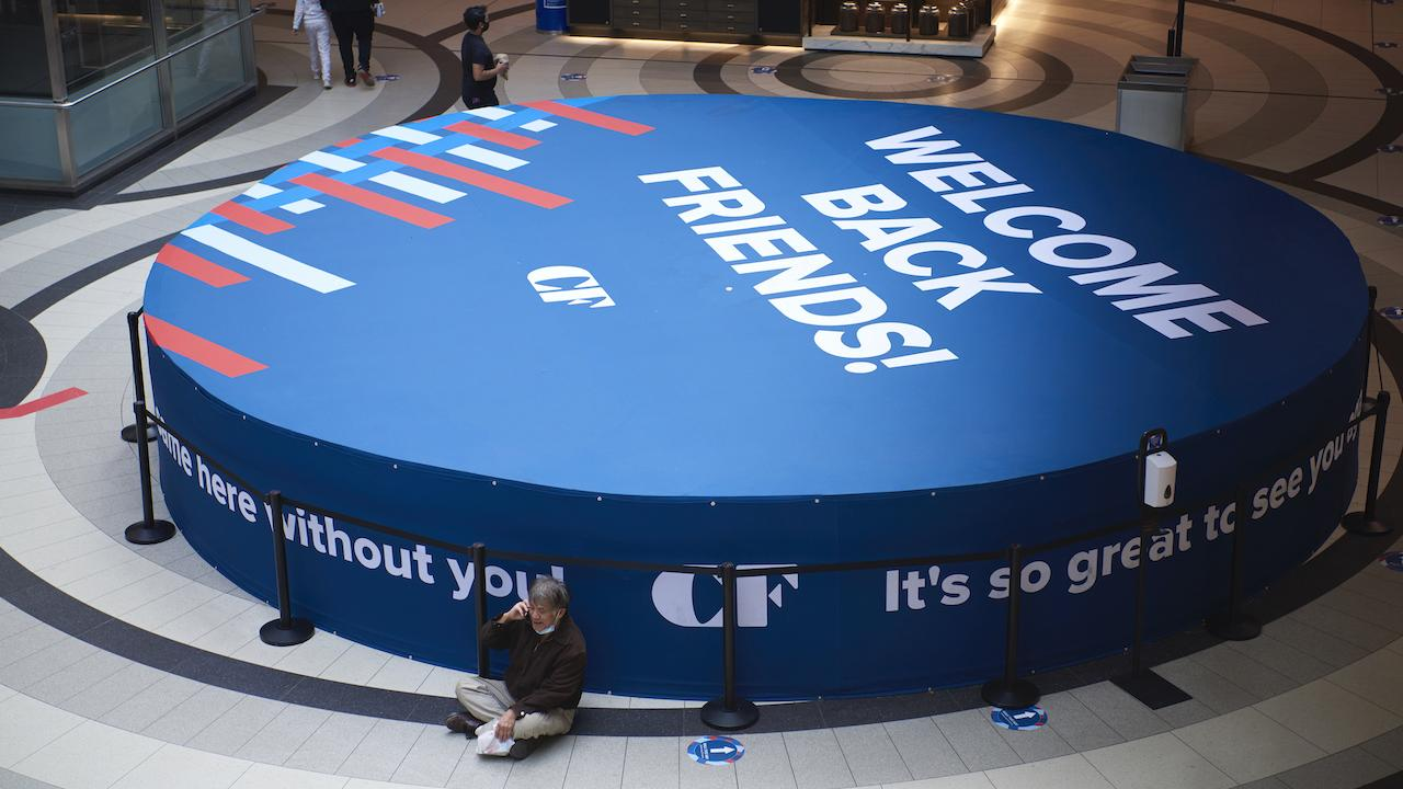 """a man sits on the floor of a mall by a large sign reading """"Welcome back friends"""""""