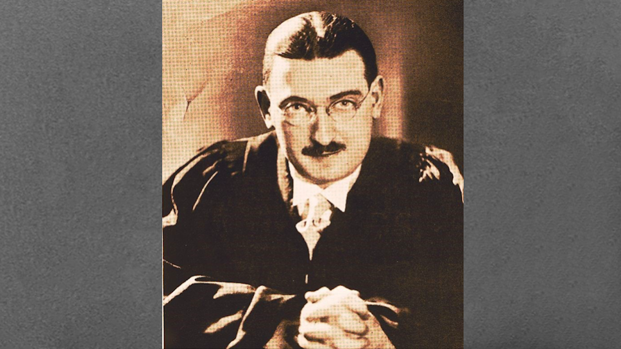 black and white photo of a man with glasses and a moustache