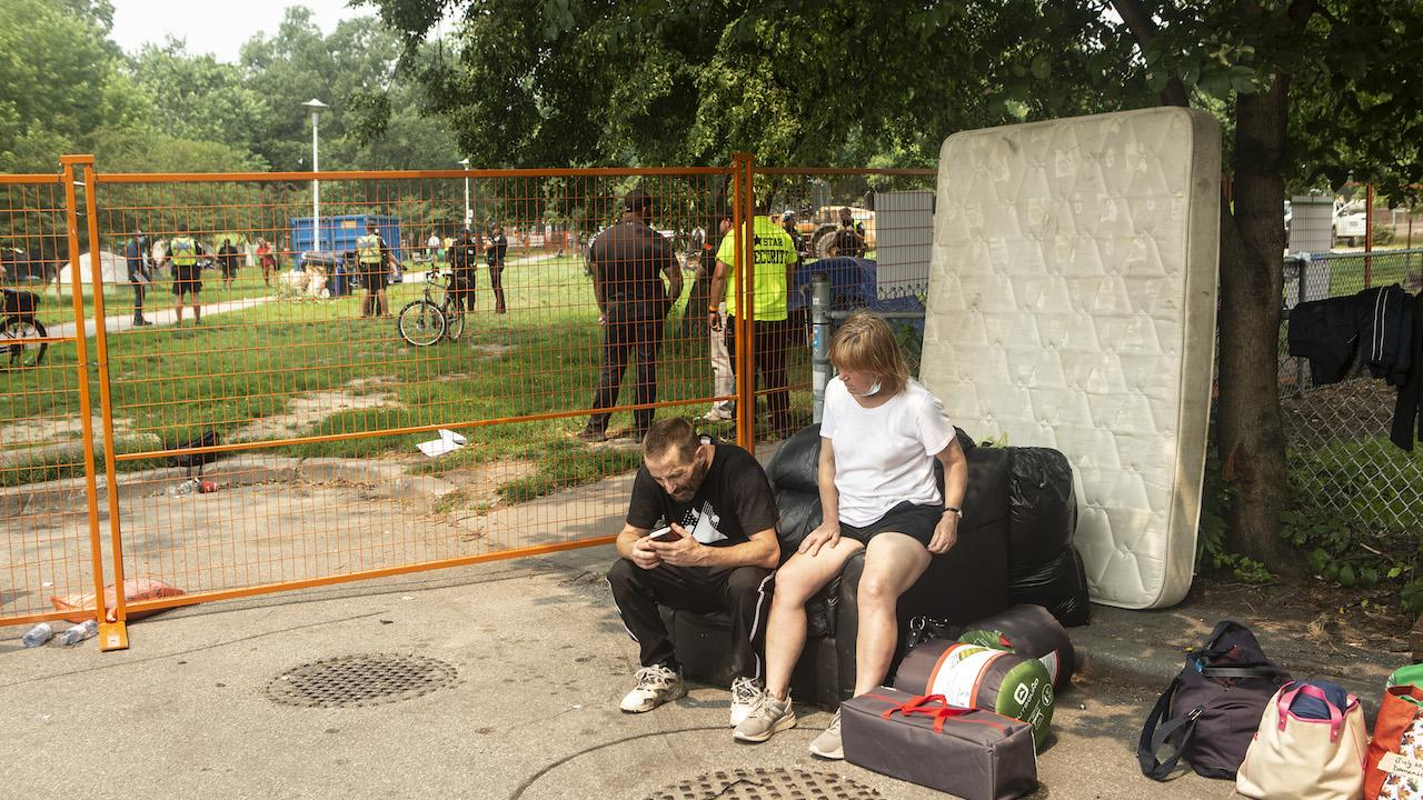 two people sit with their belongings in front of a fence, behind which police stand