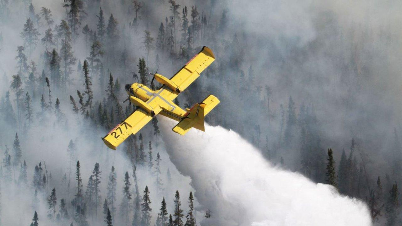 a yellow plane flying above trees consumed in smoke