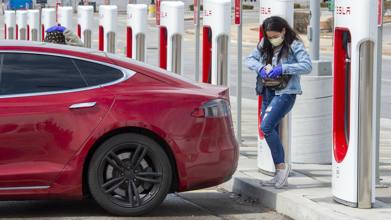masked woman and a red car in front of EV charging stations