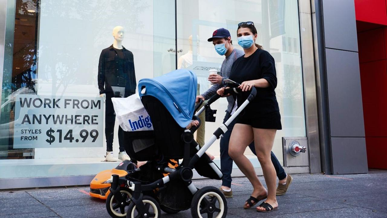 A woman wearing a mask pushes a stroller as a man wearing a mask walks with her.