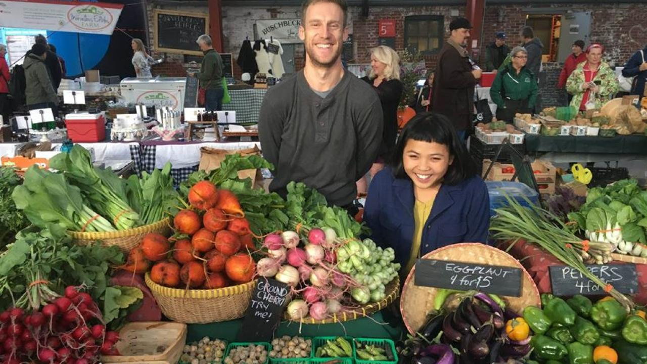 two people showing off fresh produce in a market