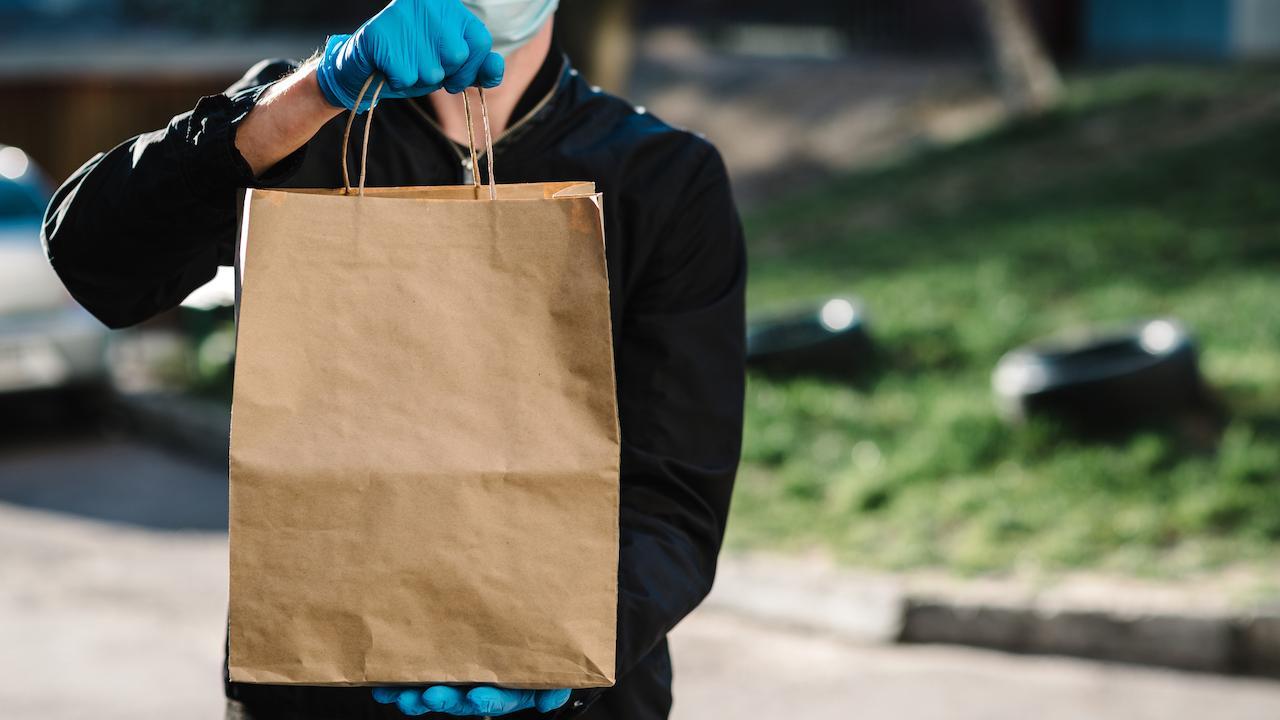 a masked man delivering food