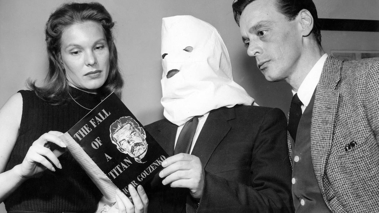 man wearing a white hood and holding a book stands between a woman and a man