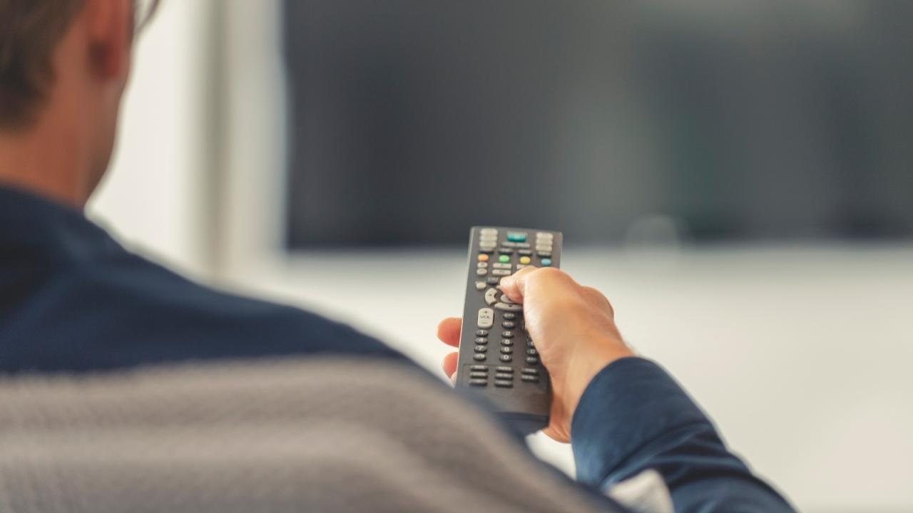 person holding a TV remote control