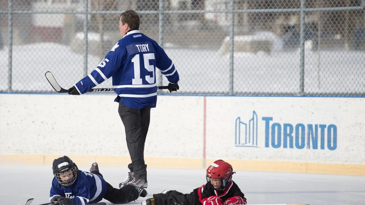 Toronto mayor John Tory on the ice with young hockey players