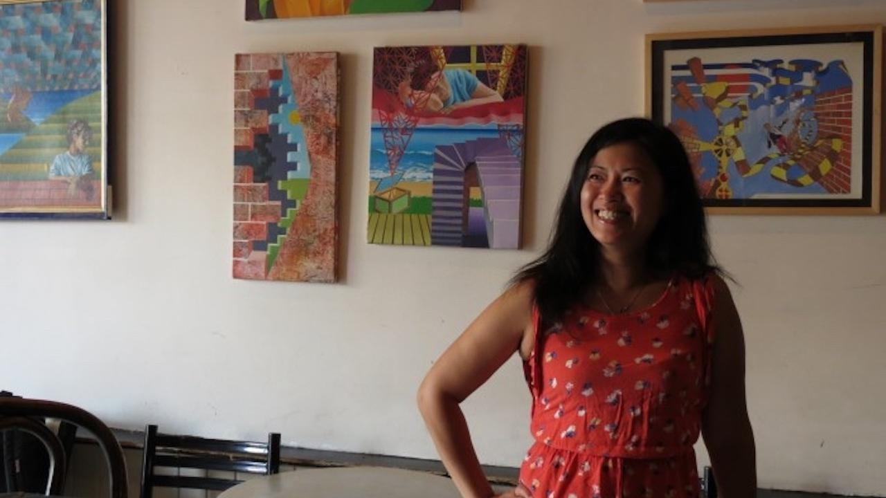 a woman with long black hair stands in front of paintings and tables
