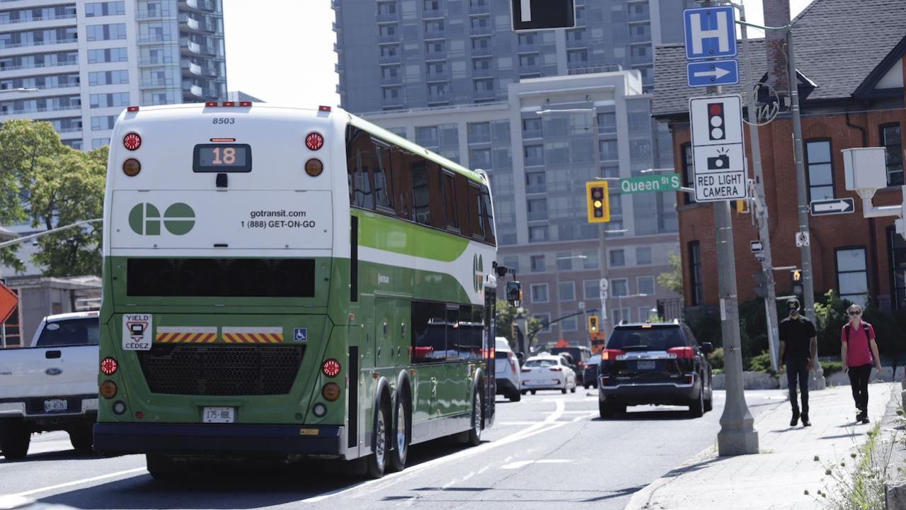 a green bus on a busy city street; two pedestrians on the sidewalk