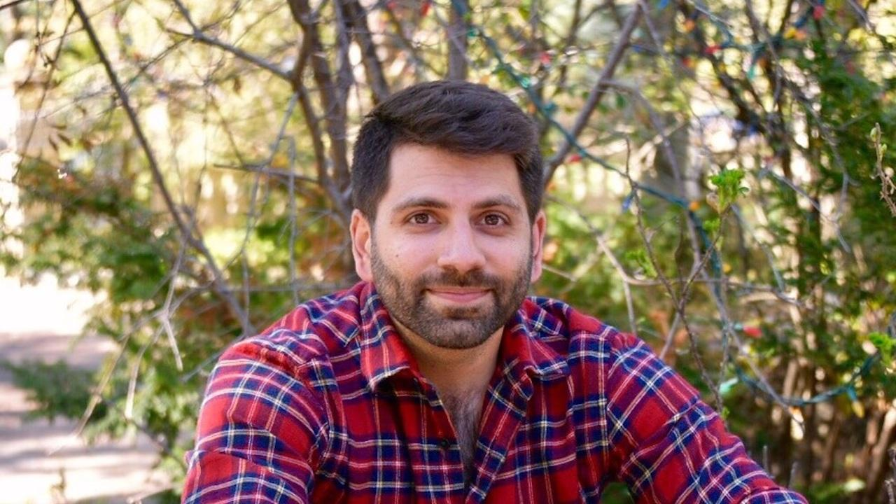 closeup of a man in a plaid shirt sitting in front of a tree