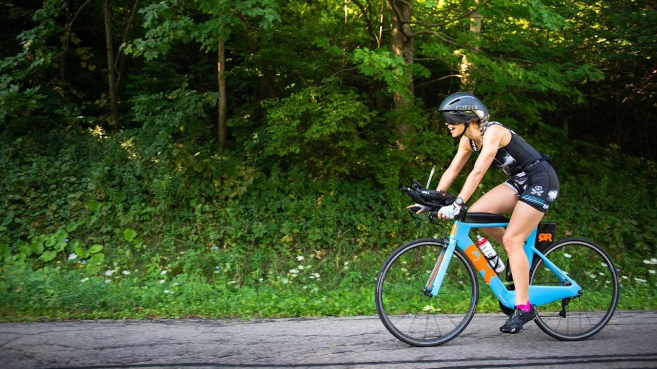 woman in helmet on a blue bicycle riding on a road past trees