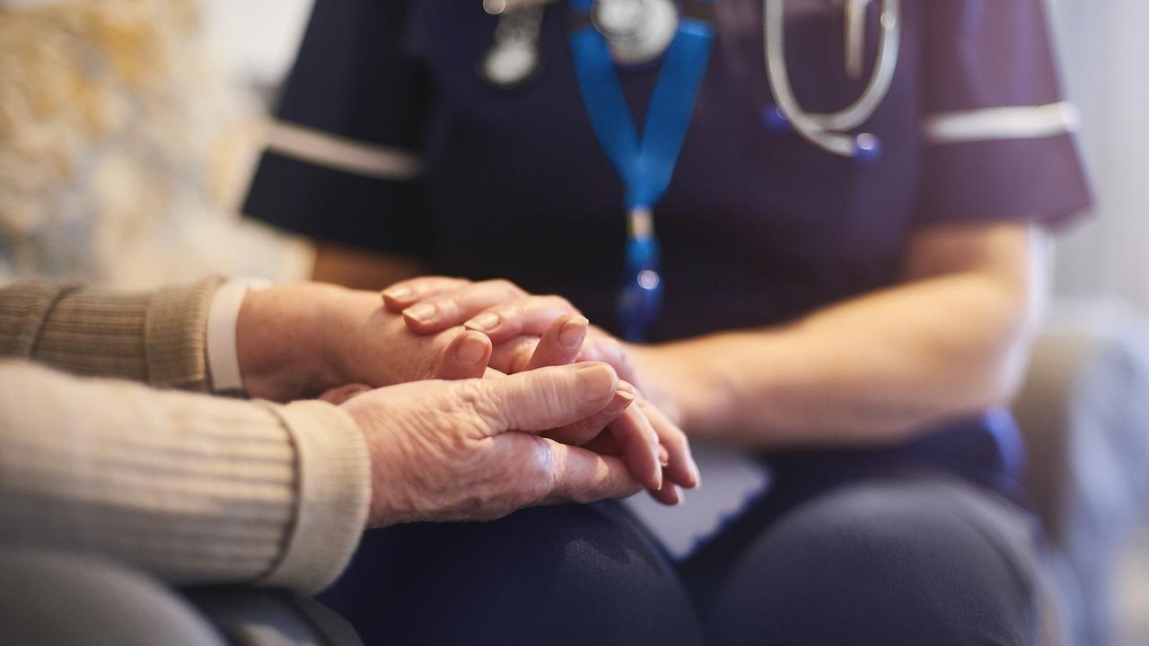nurse holds a woman's hands