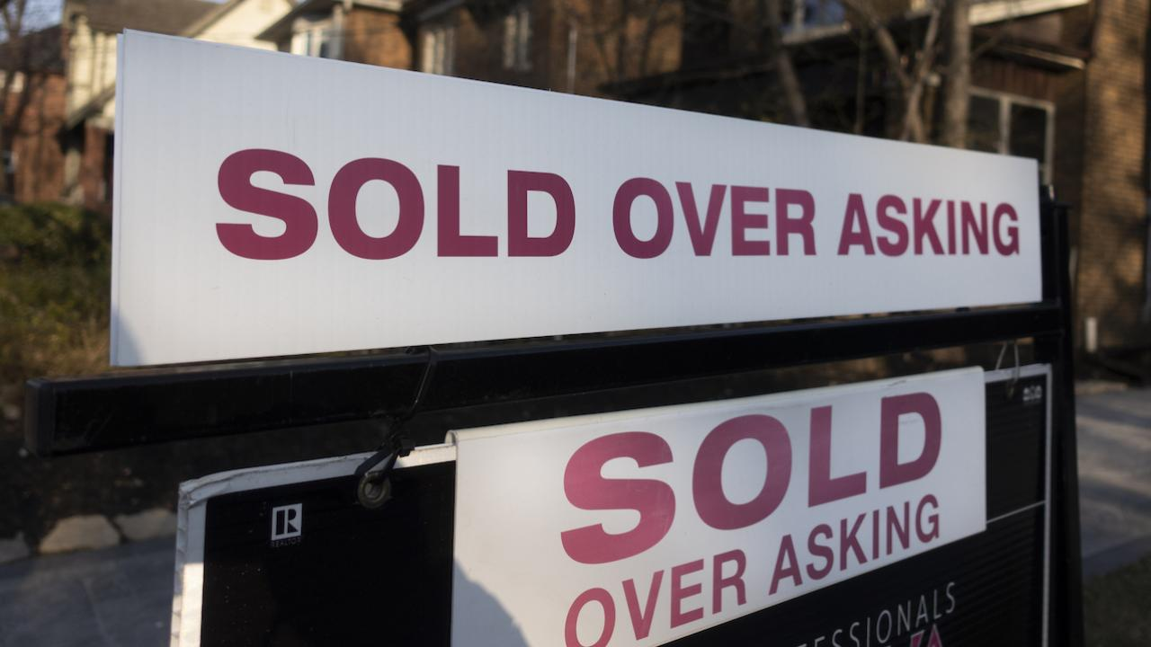 """two signs reading """"sold over asking"""""""