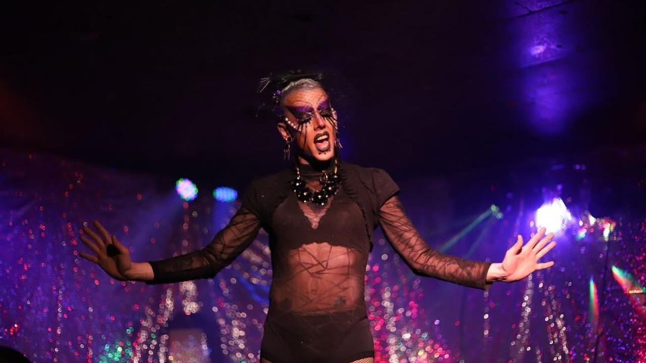 Person in elaborate dress and makeup performs on a stage.