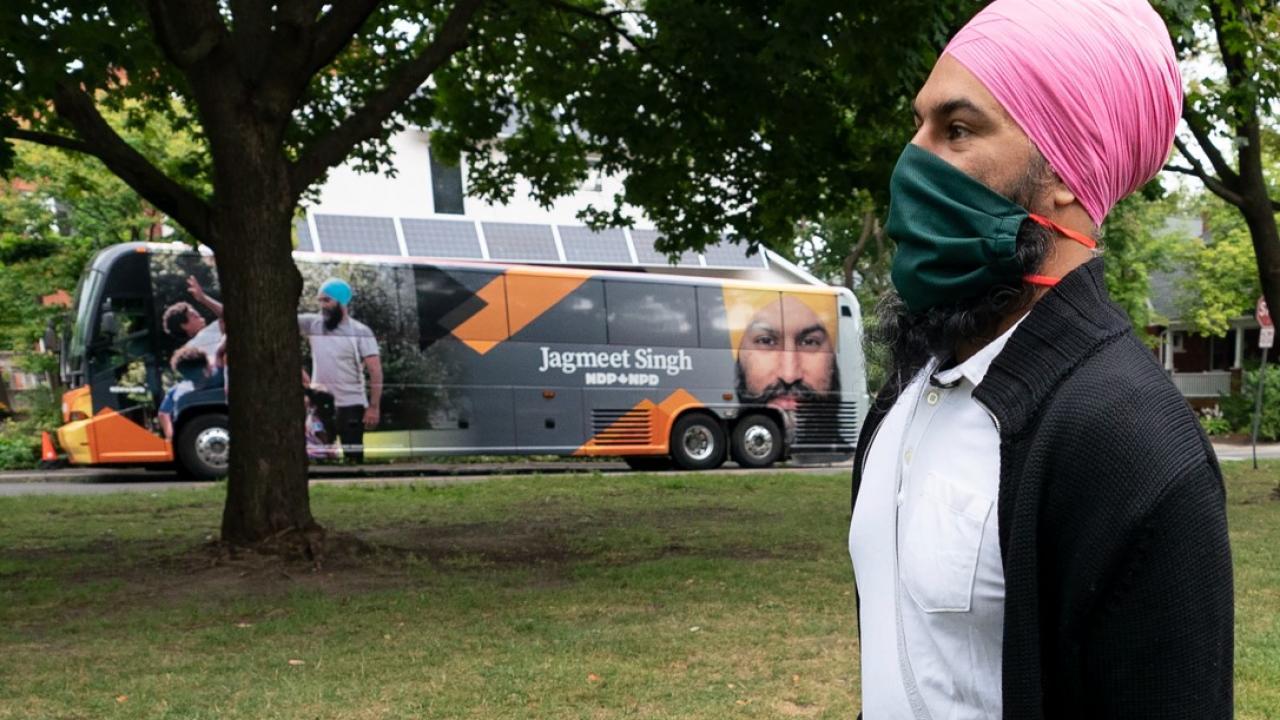 Jagmeet Singh, wearing mask, walks past his campaign bus.