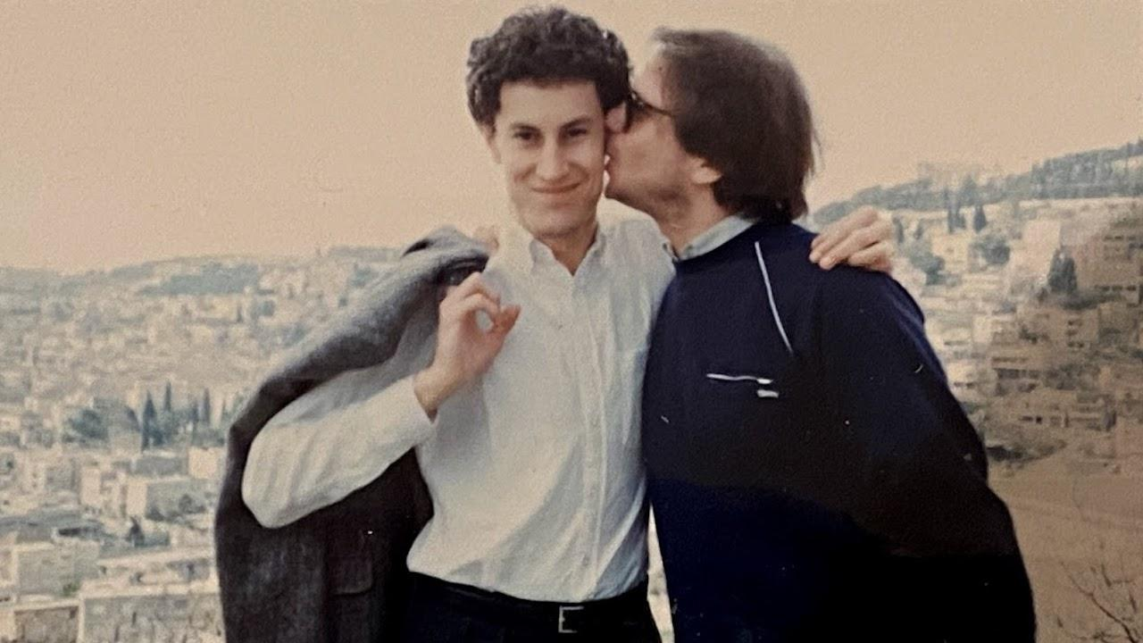 a man in sunglasses kisses another man on the cheek