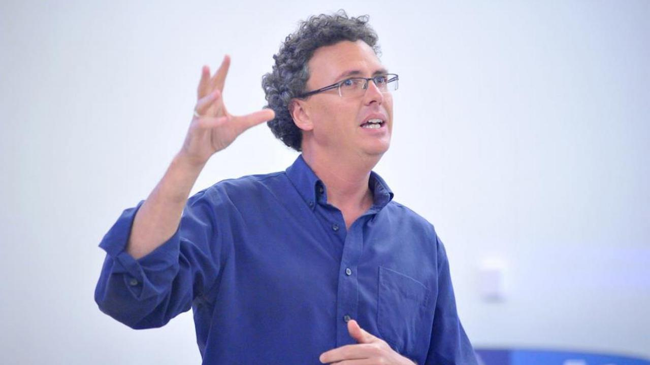 man in blue button-up shirt and glasses with one arm raised