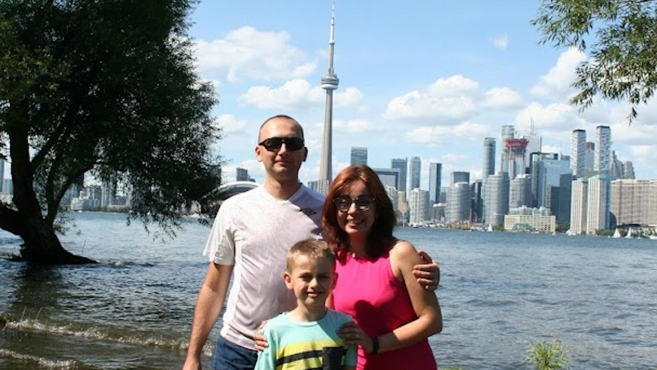 a woman and man with a young boy in front of the CN tower