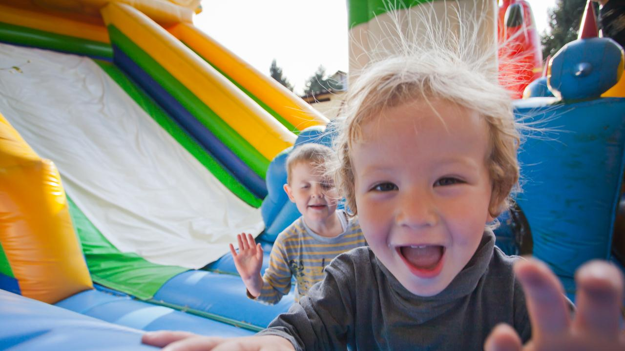 two toddlers waving and playing in a bouncy castle