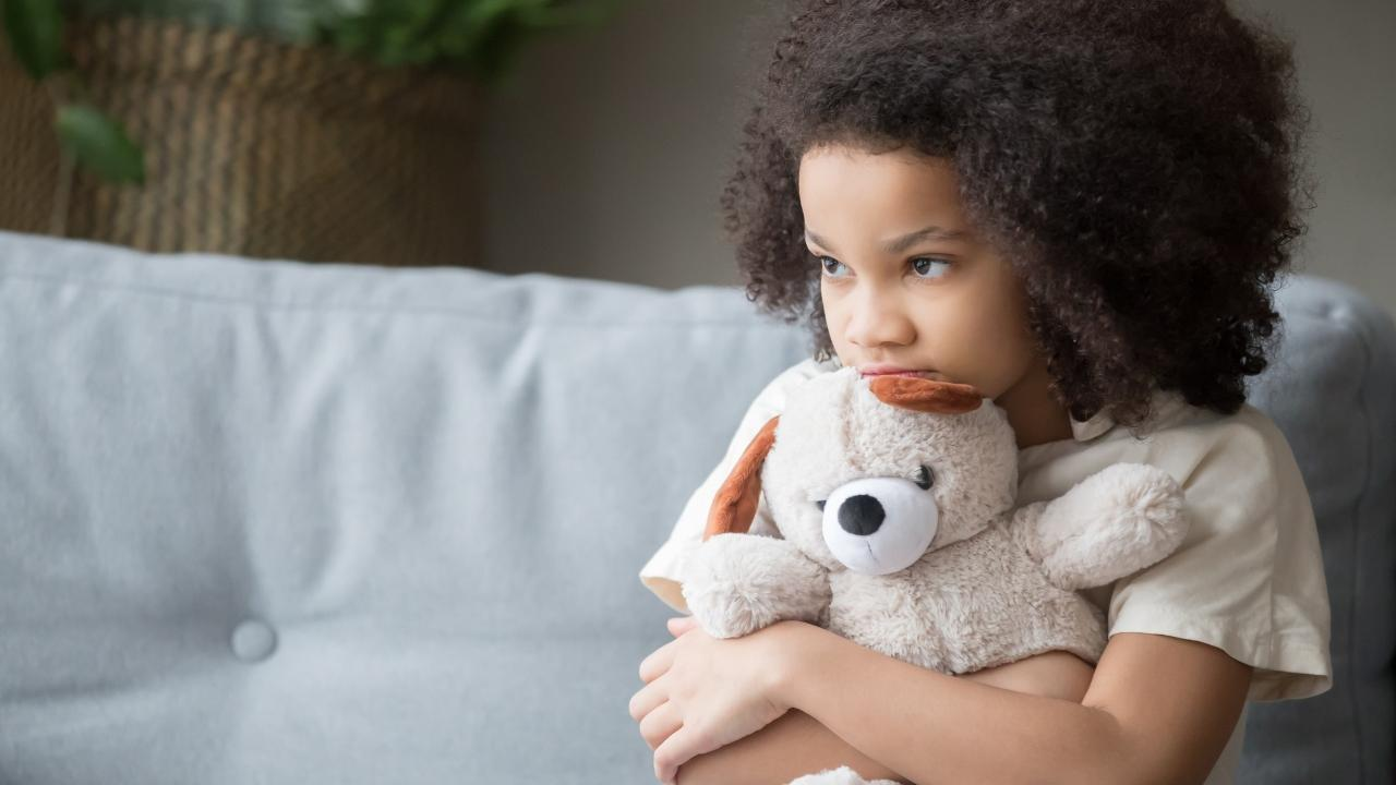 a child looking loney holding a teddy bear