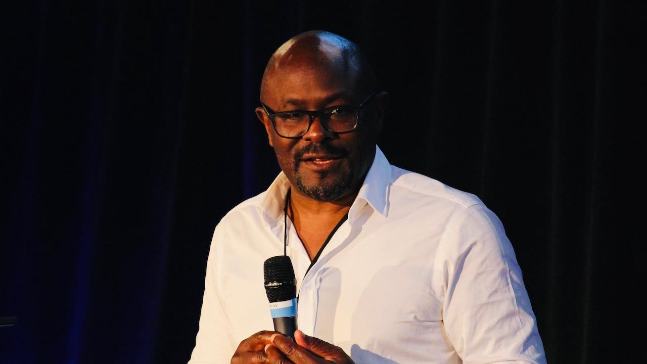 man in glasses and white shirt holding a microphone