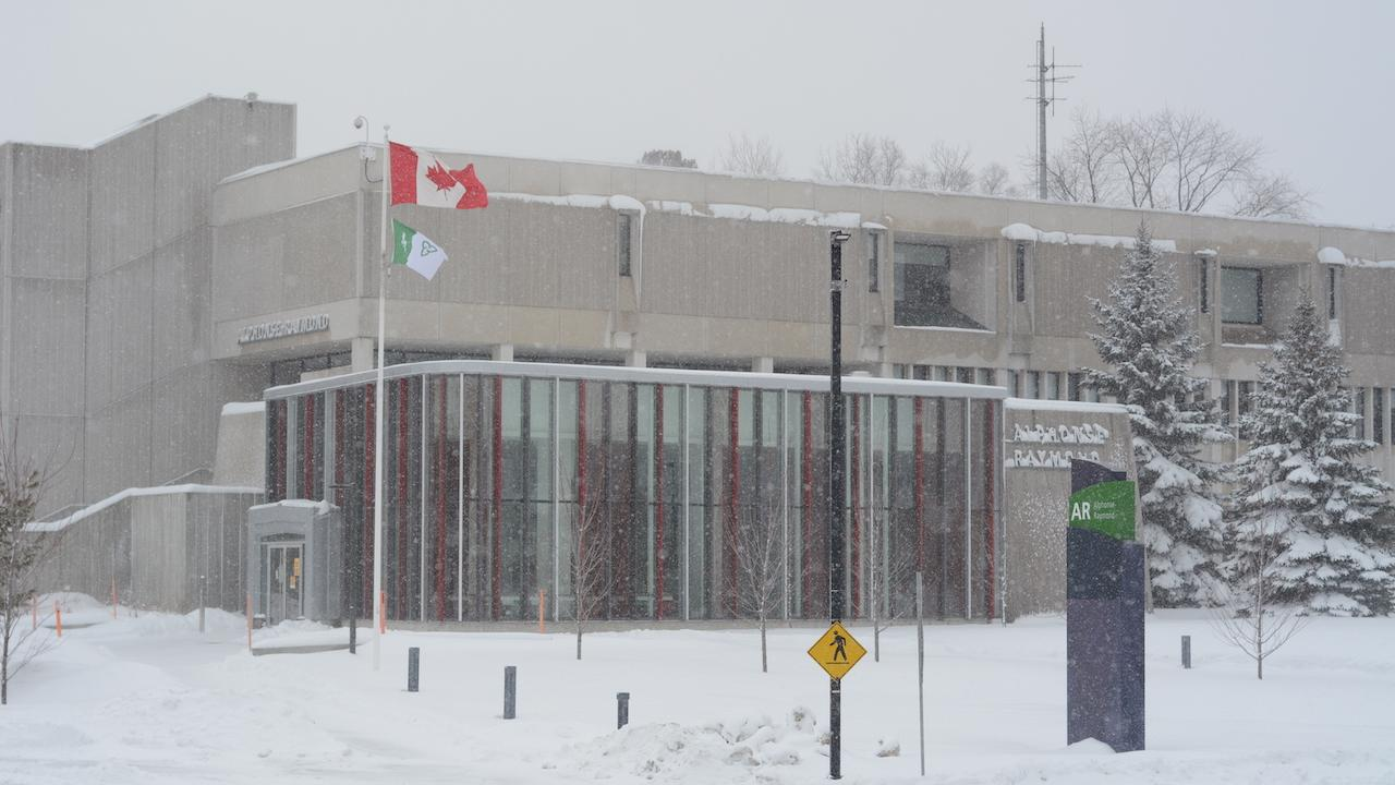a low-lying university building in the snow, with a flag outside