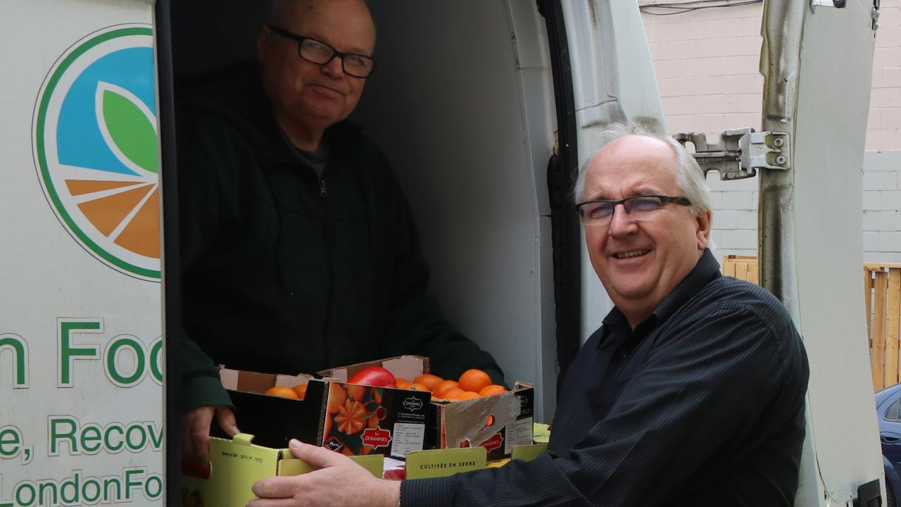 Man holding box filled with food hands it to man standing in the back of a van.