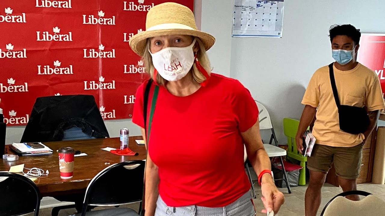 """women in red t-shirt, mask, and hat standing in front of a banner saying """"Liberal"""""""
