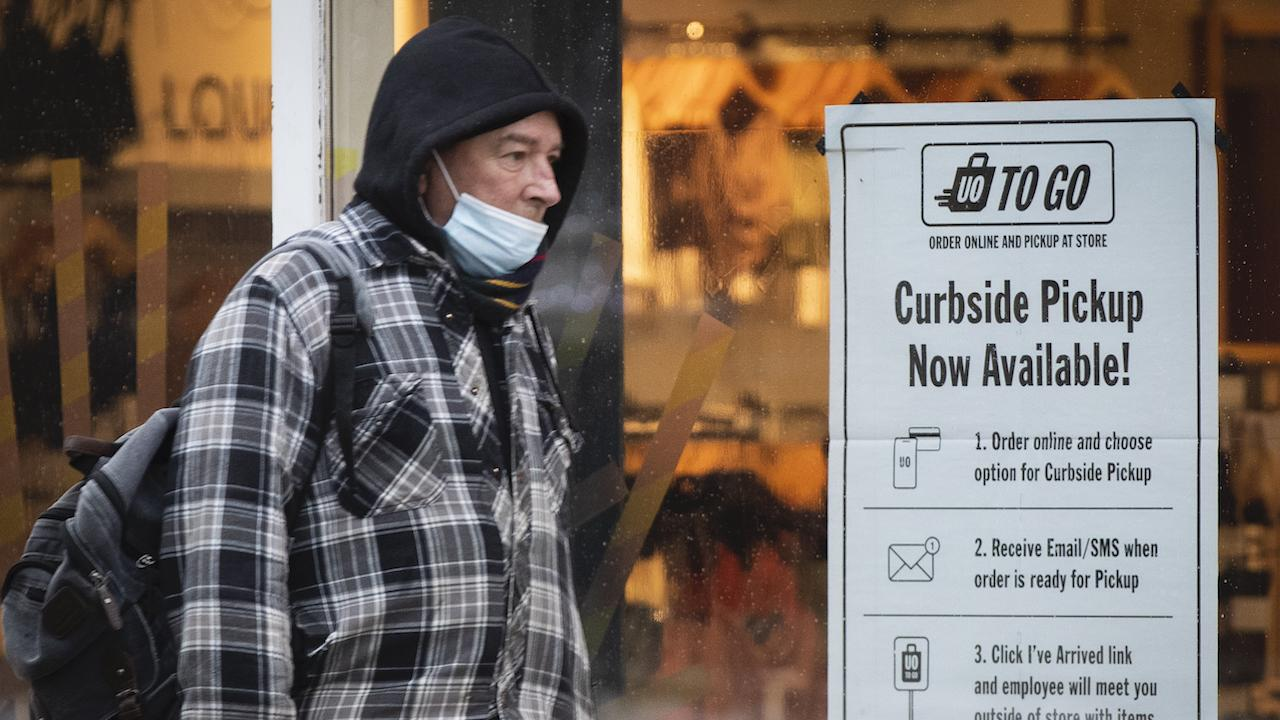 a mask-wearing man walks past a sign advertising curbside pickup