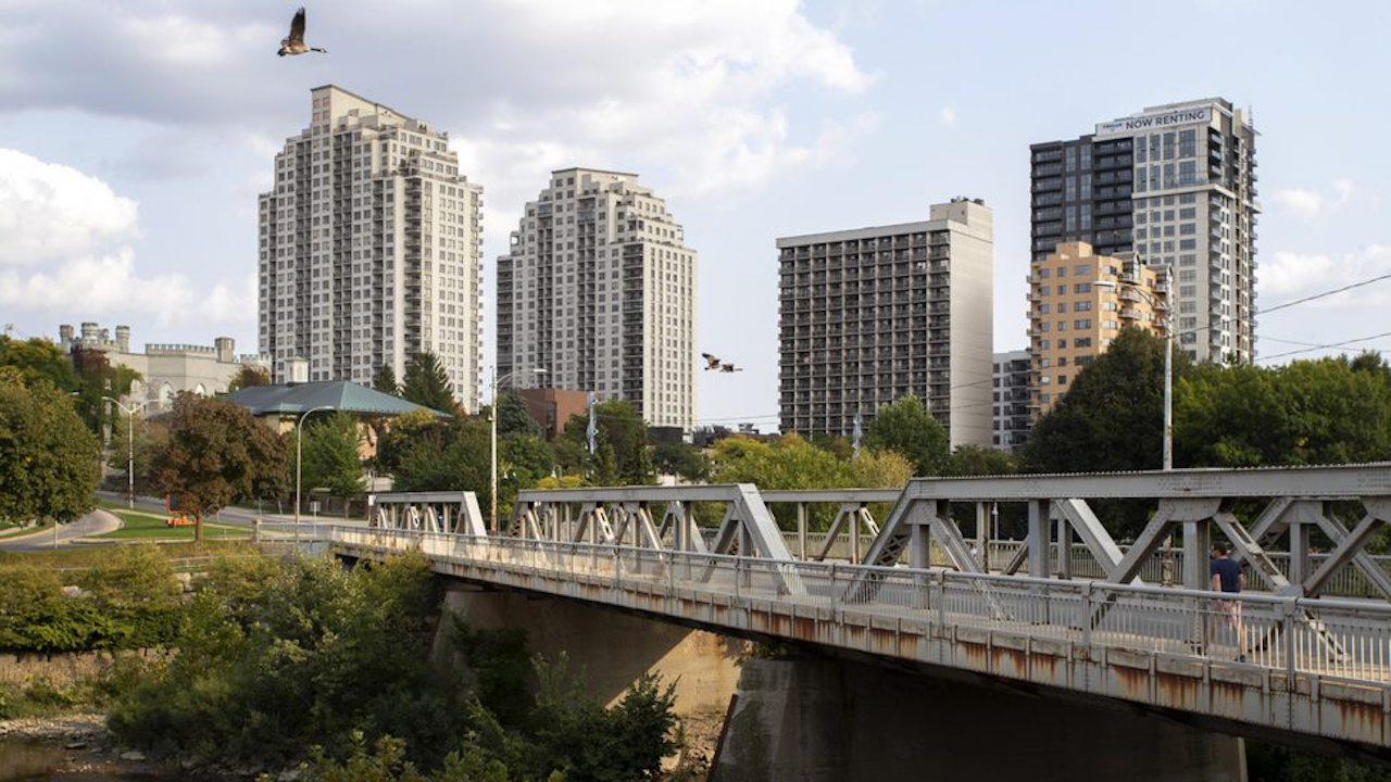 a bridge in front of a group of tall concrete buildings