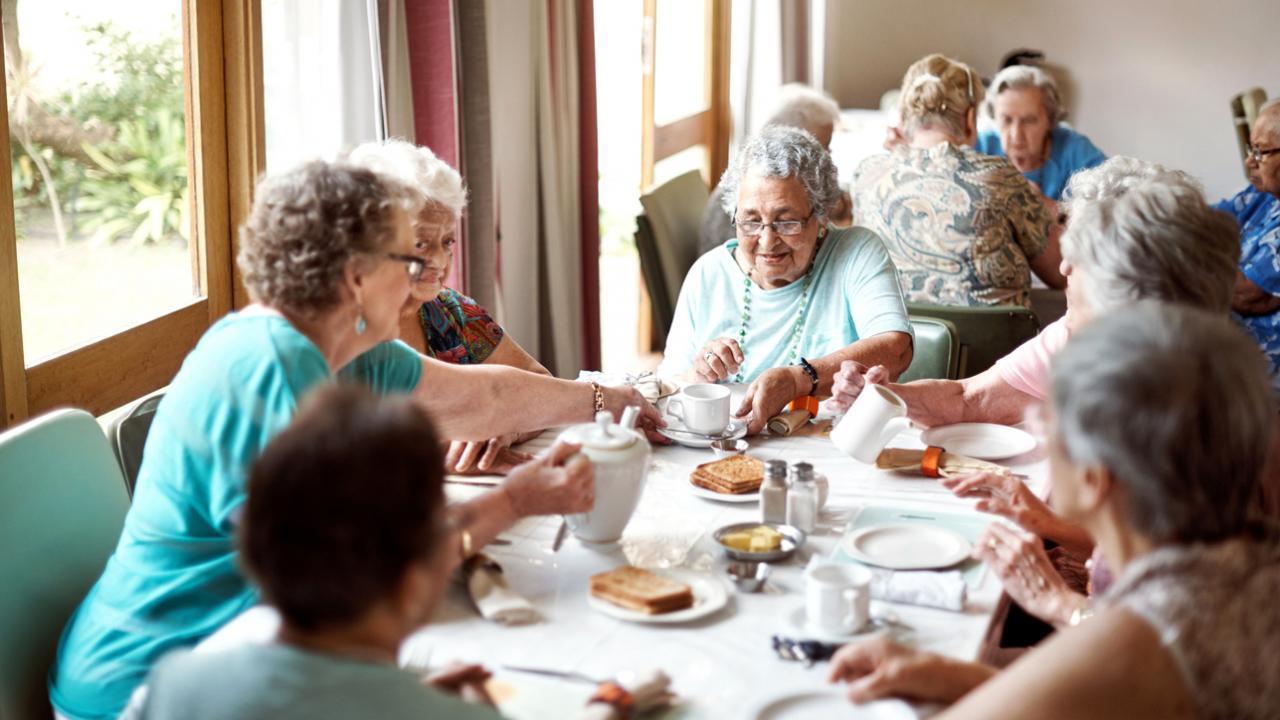 Elderly people eating a meal together