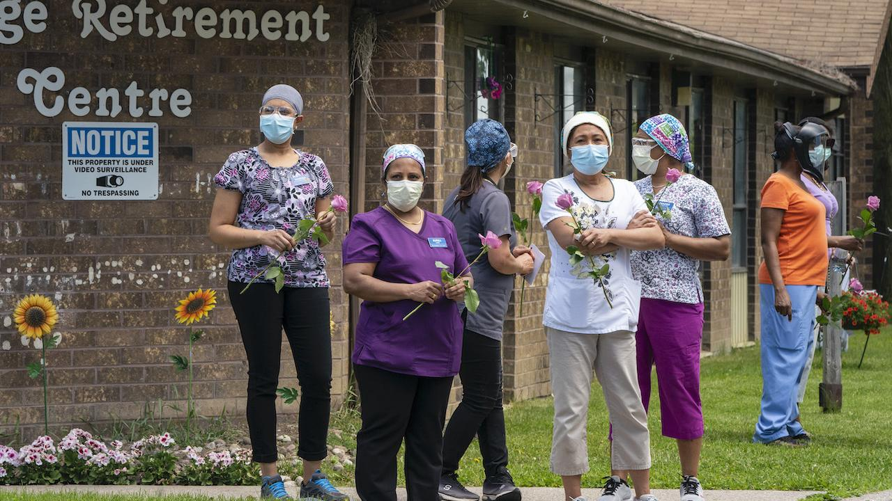 workers stand outside a LTC home wearing masks and holding flowers