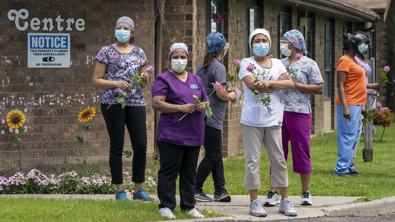 masked health-care workers standing in front of a brick building