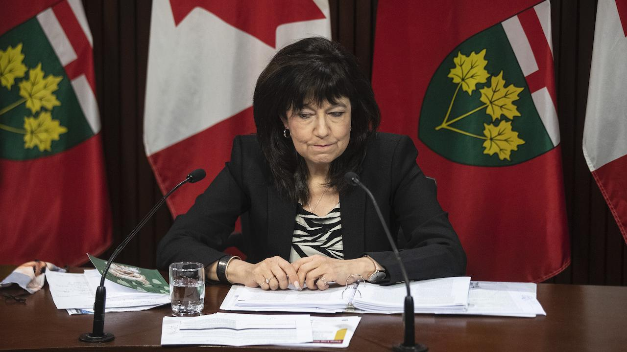 a woman sits at a desk in front of flags