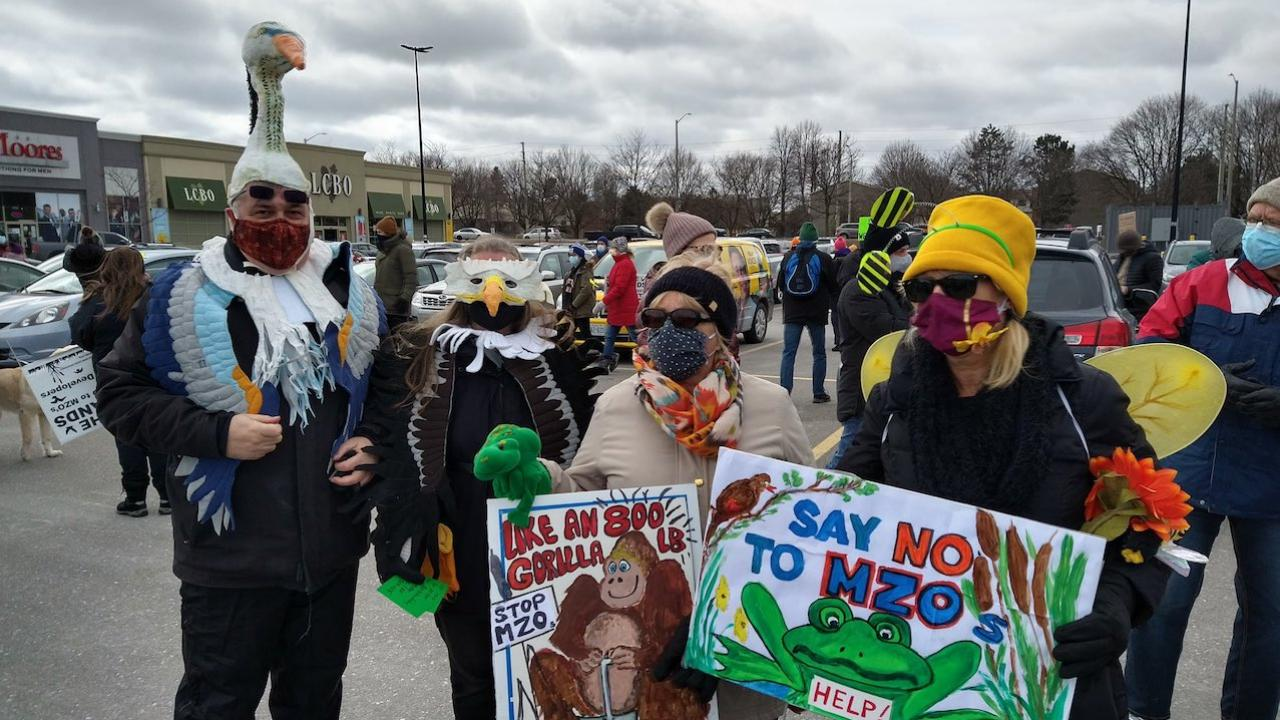 three people dressed up as colourful animals hold anti-MZO signs