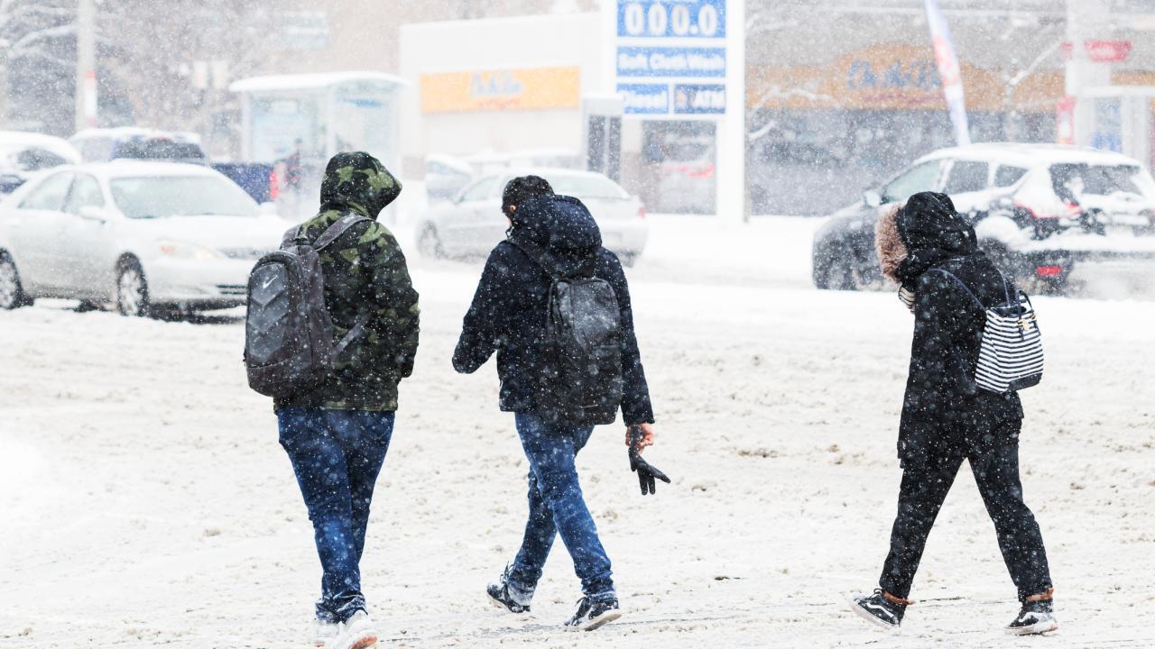 Three people cross a street during heavy snowfall.